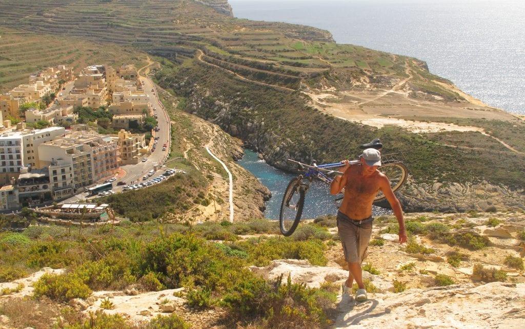 Mann trägt Fahrrad über der Bucht von Xlendi auf Gozo