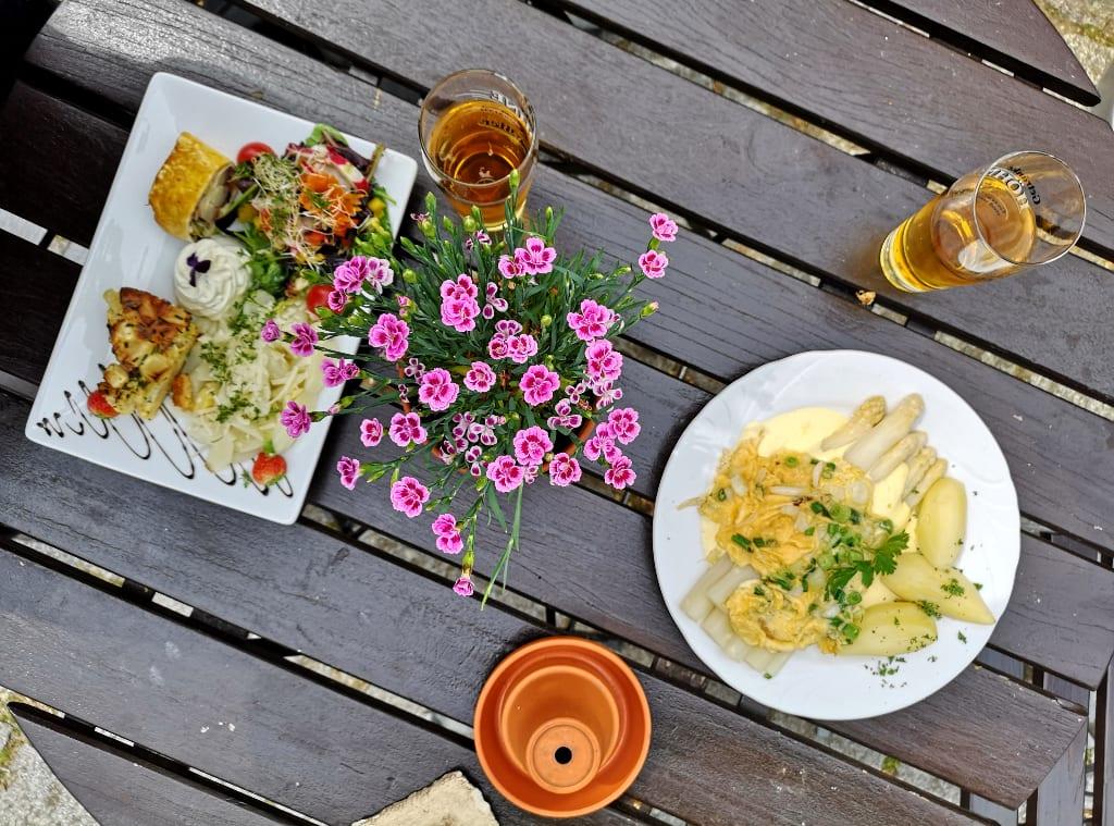 Teller mit Spargel und Blümchen auf einem Holztisch