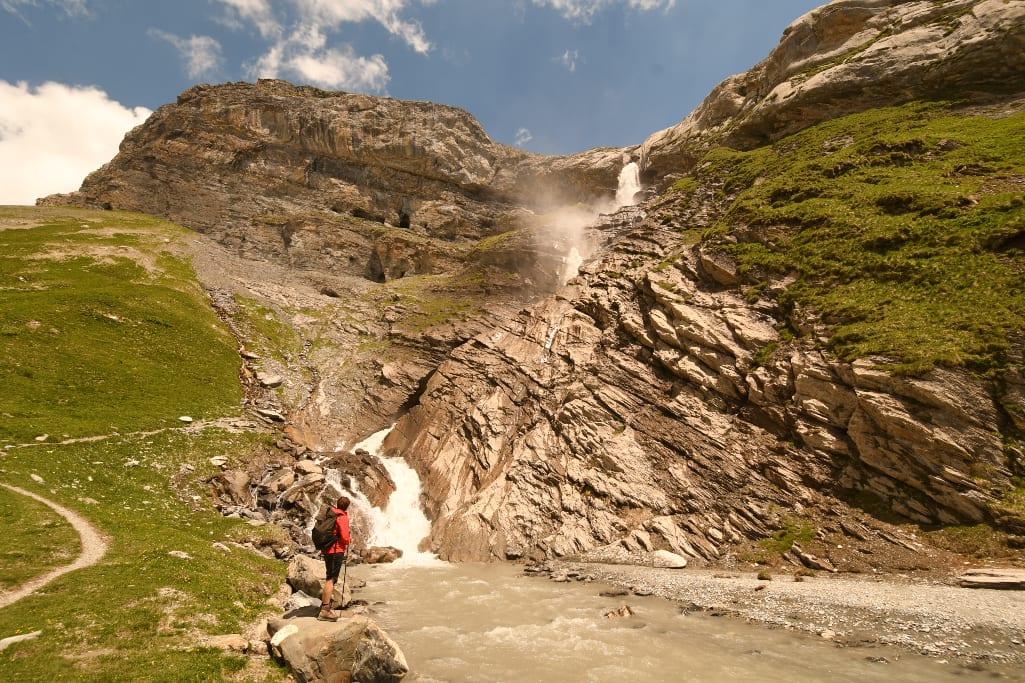 Wasserfall, davor Frau in roter Regenjacke