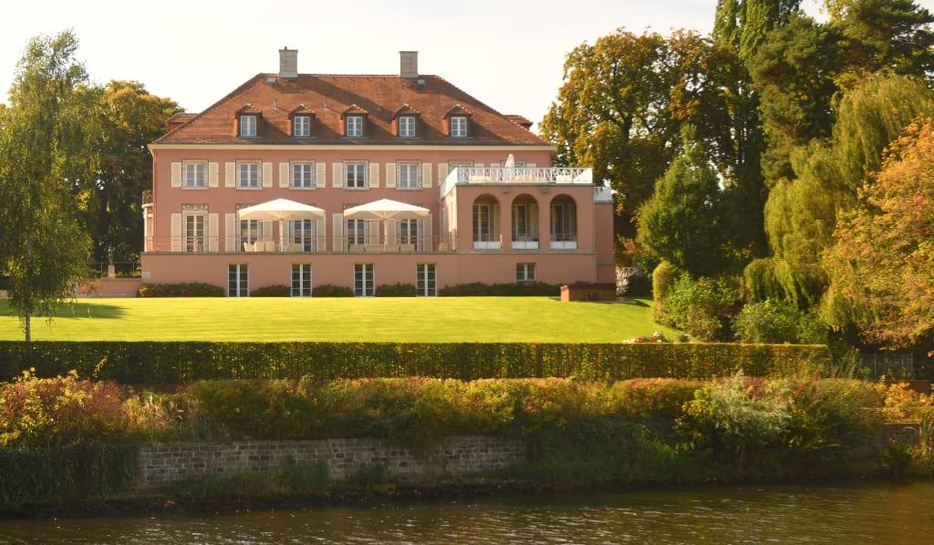 Rosafarbene Villa an einem Gewässer