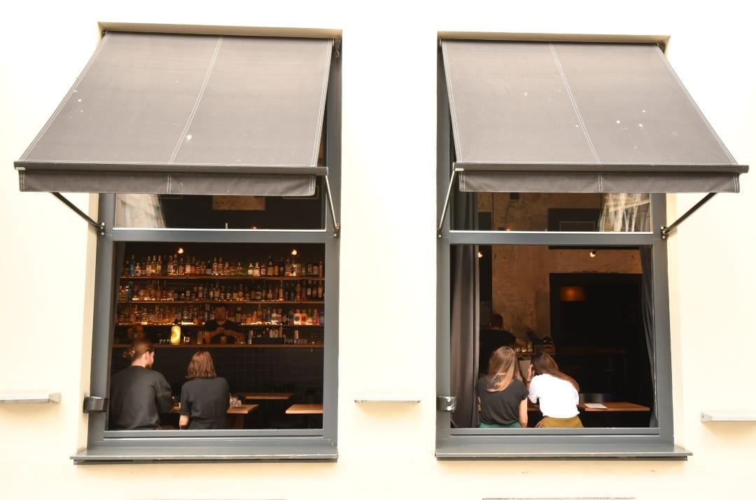 Leute sitzen am Fenster einer Bar