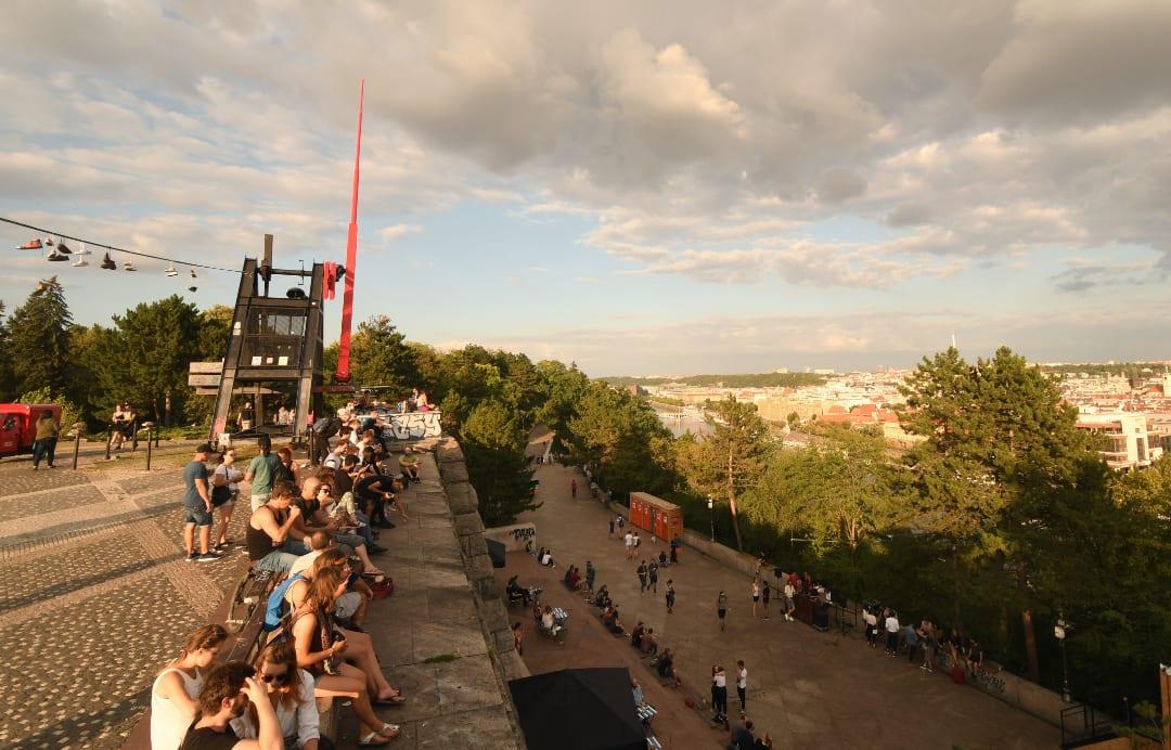 Junge Leute sitzen bei einem Metronom und blicken über die Stadt