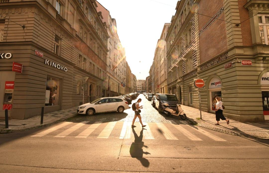 Frau läuft im Gegenlicht über Straße mit historischen Häusern