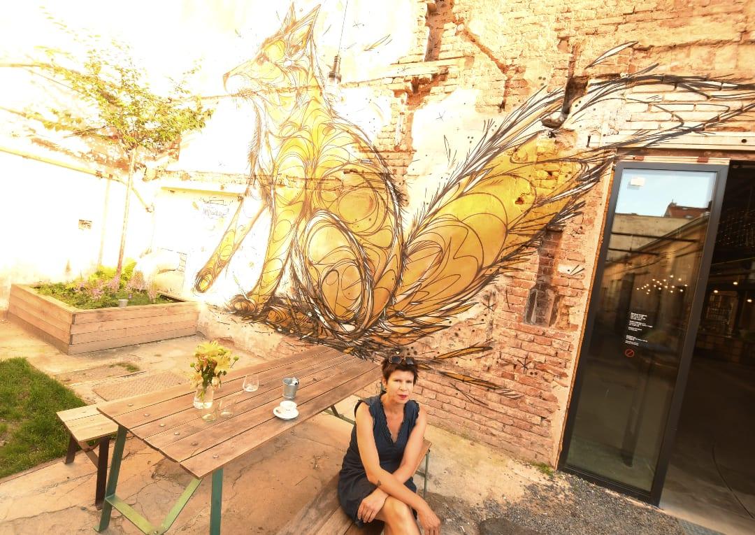 Frau sitzt auf Bierbank vor Streetart